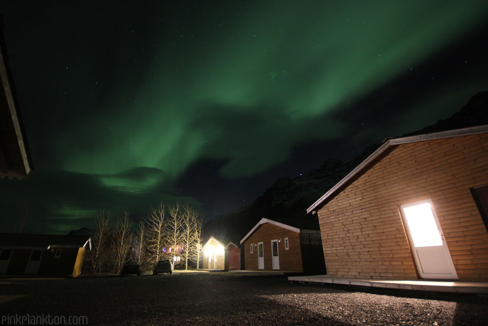 Northern Lights/aurora borealis over cabins in Iceland