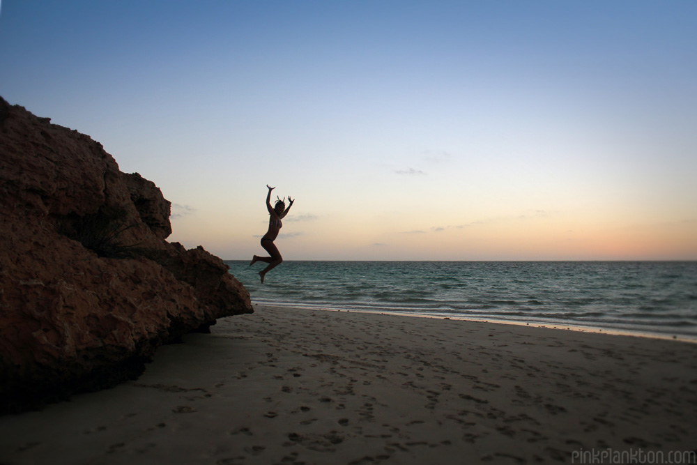 person jumping from cliff on beach