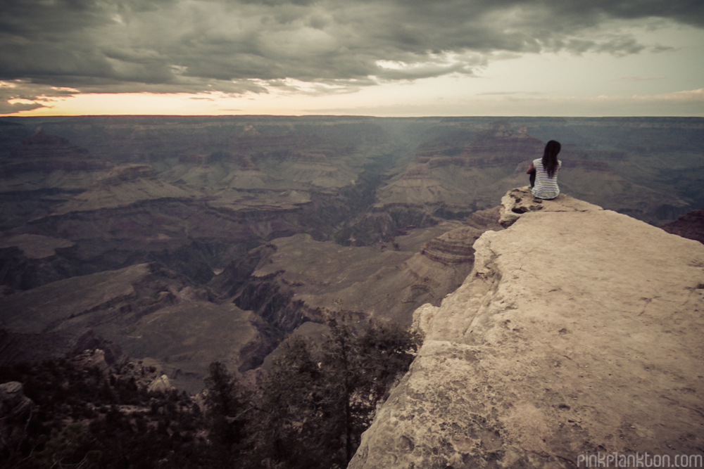 girl sitting on edge of the Grand Canyon at sunset