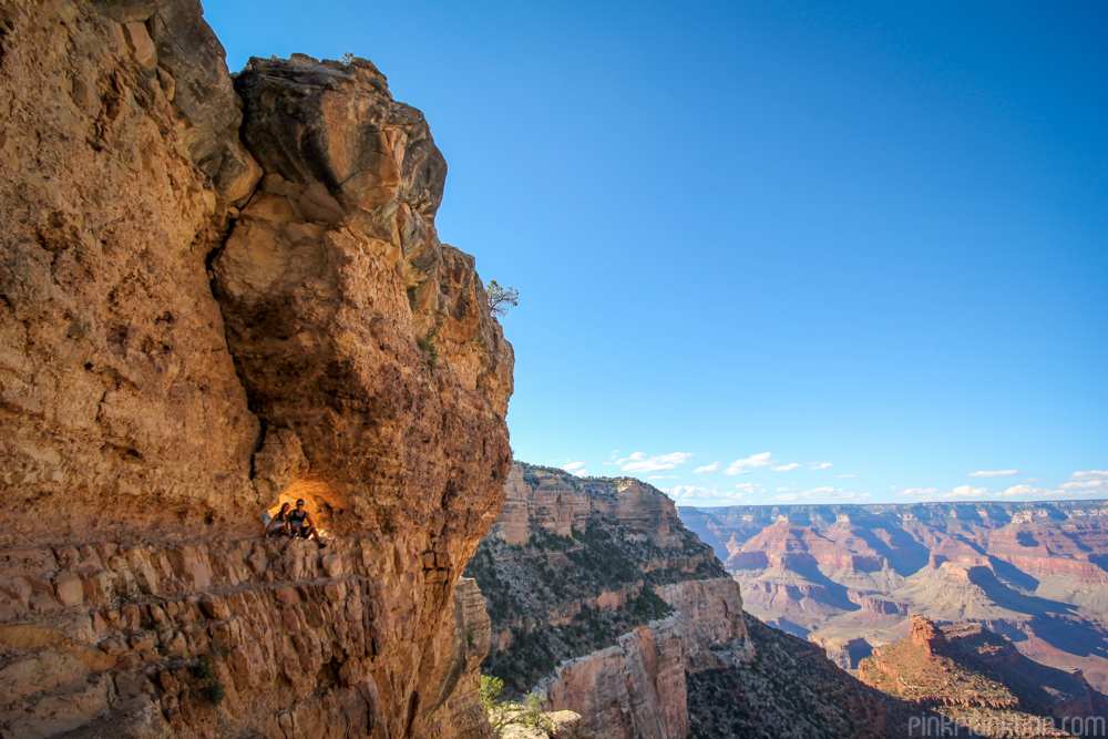 two people sitting in a window in the inner rim of the Grand Canyon in Arizona