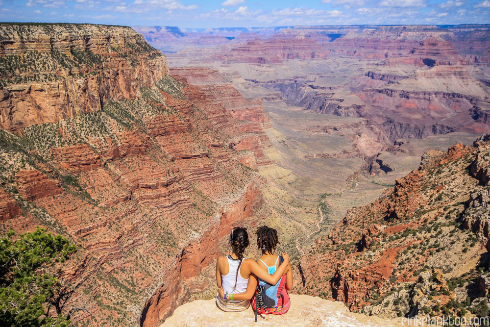 2 girls sitting overlooking the Grand Canyon