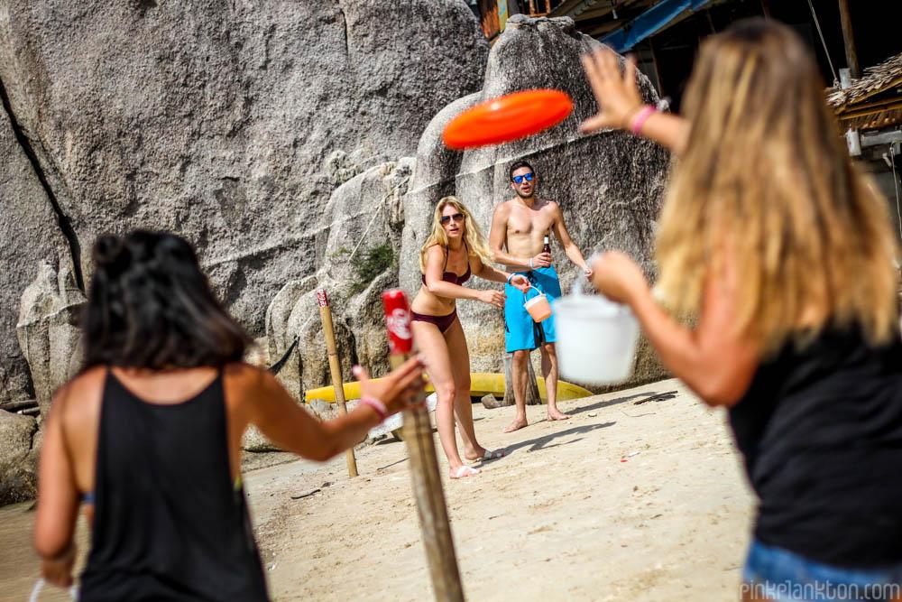 people playing beersbie on the beach