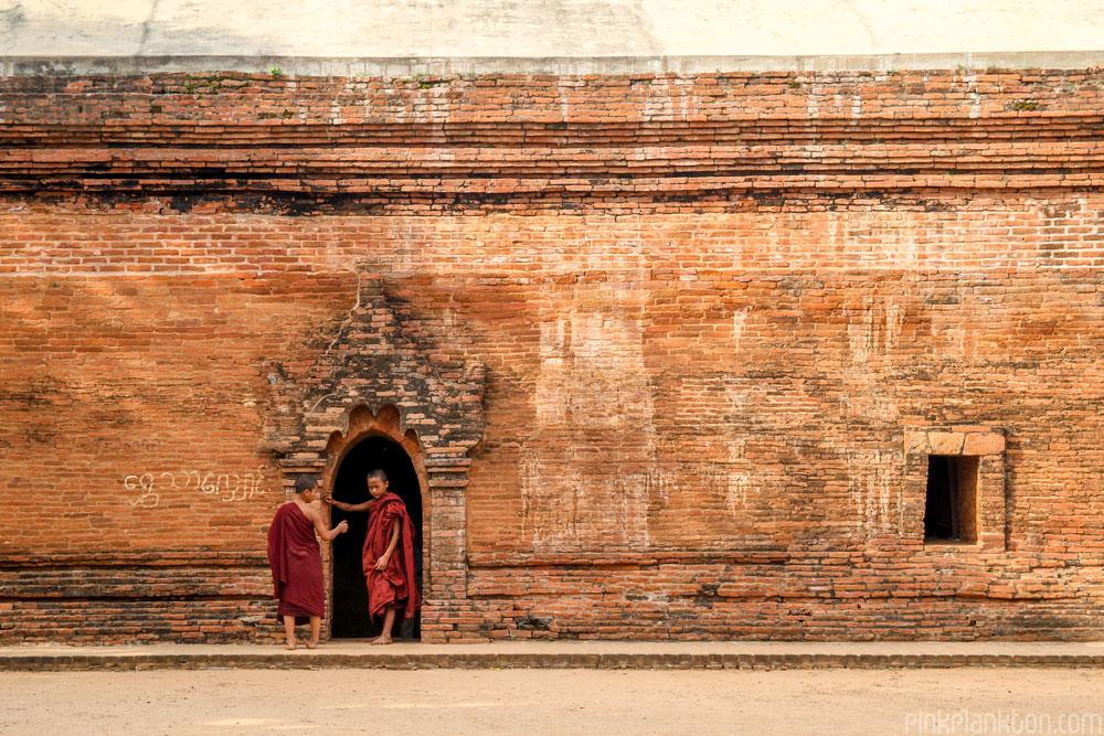 monks standing outside ruins in Bagan