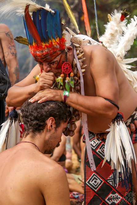 indigenous man performing blessing ceremony on man at Tribal Gathering Festival in Panama
