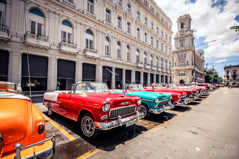 colorful classic cars in Havana Cuba in front of colonial architectural building