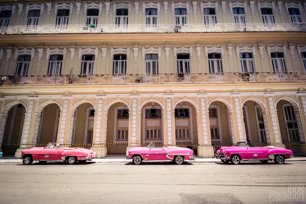 3 pink classic cars in Havana Cuba in front of colonial architectural building