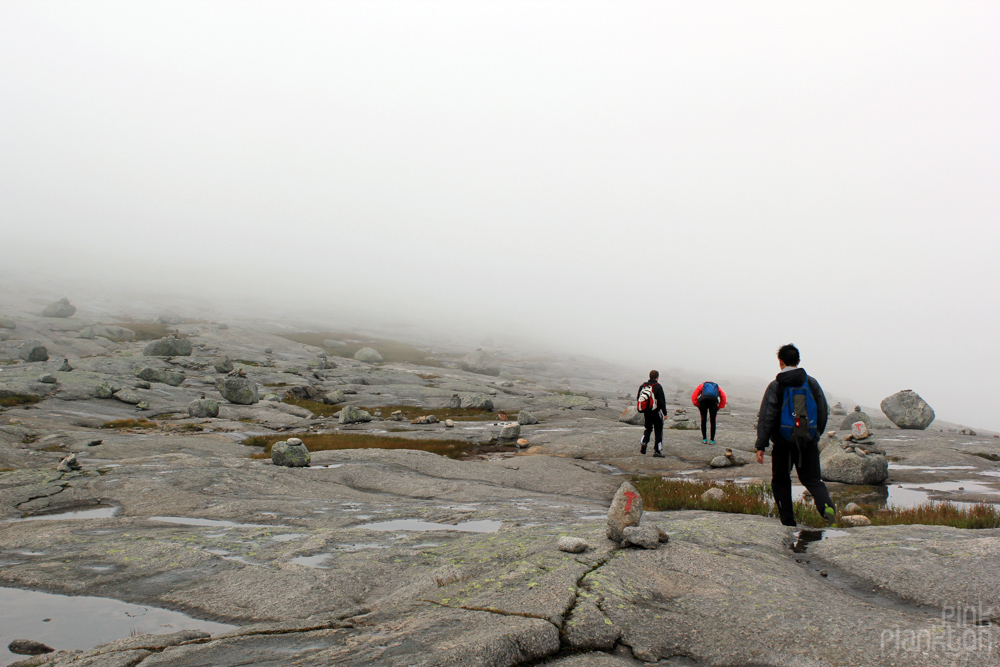 hikers in rocky cloudy scenery in Norway
