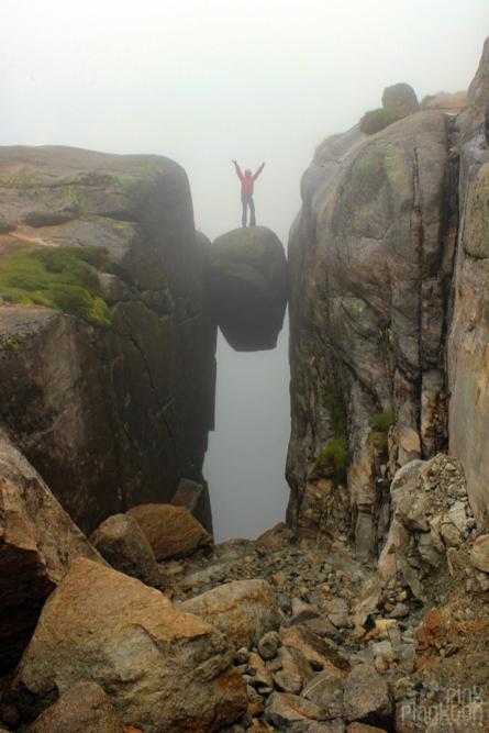 woman standing on Kjeragbolten in clouds in Norway