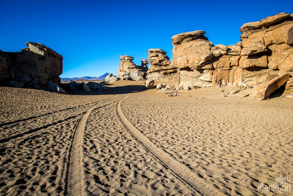 rock formations and sand road in Bolivia's desert