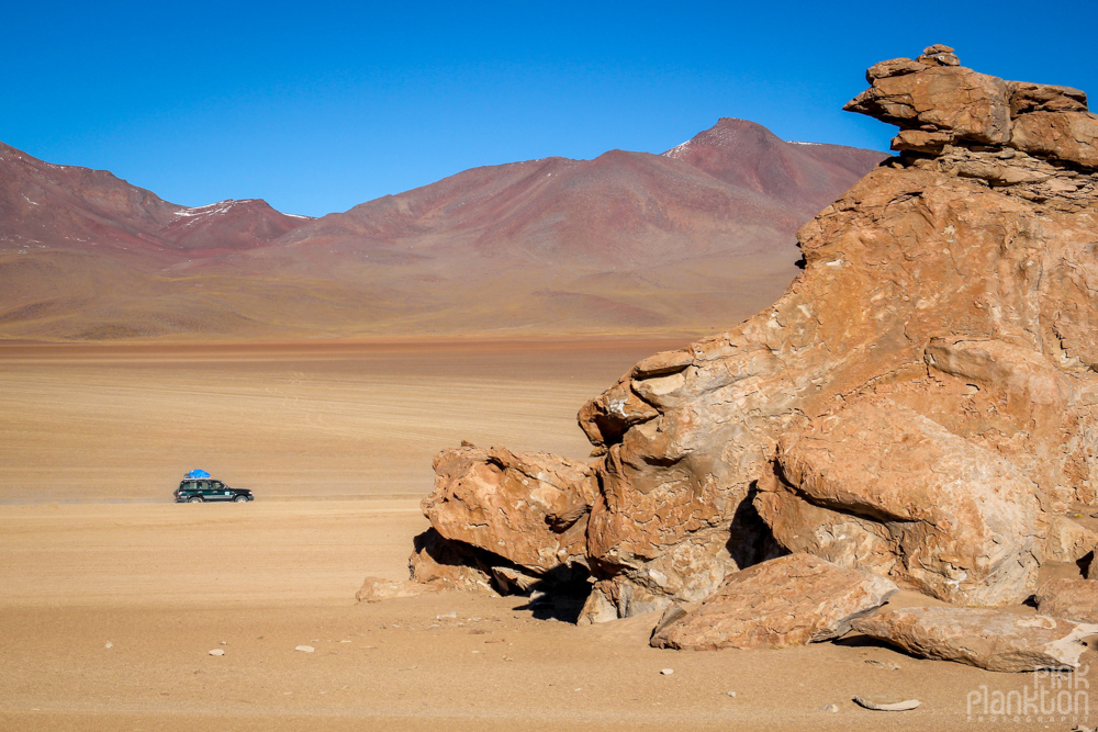 jeep and rock formations in Bolivia's desert