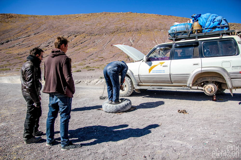 fixing a flat tire on 4WD jeep in Bolivia's desert