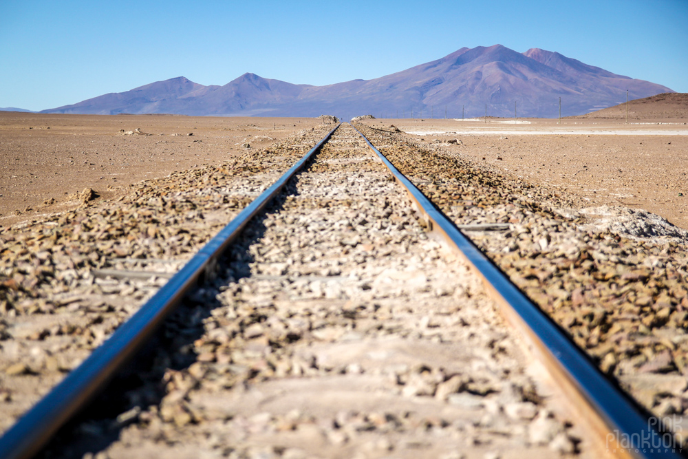 train tracks and distant mountains in Bolivia's desert