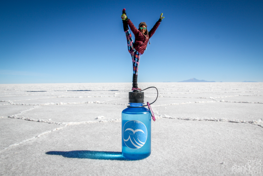 person doing Y stand on top of Nalgene bottle on Bolivia's Salar de Uyuni