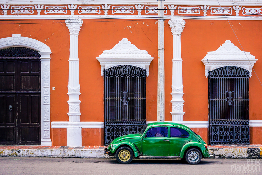 colorful orange buildings and green old school car in Campeche