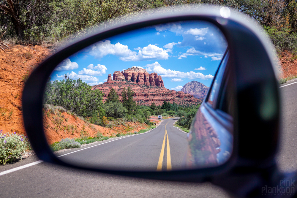 road and red rocks of Sedona in car mirror